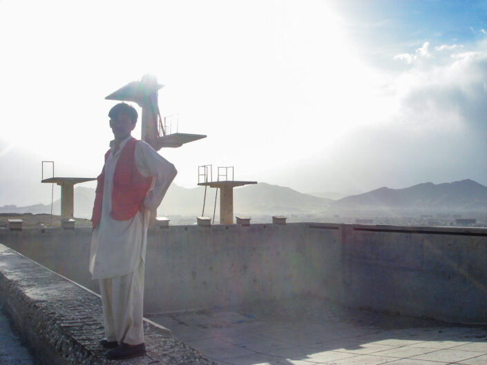 Young male in traditional Afghan dress stands by the side of an empty swimming pool with diving boards behind him.