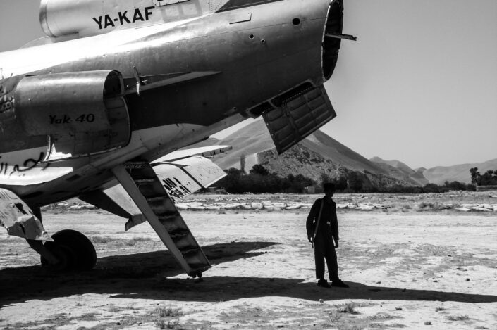 Rear end of at the fuselage of a commercial plane on an airfield with a man standing underneath, in the shade, to escape from the sun