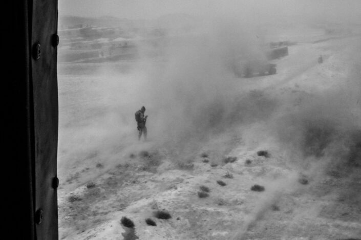 Spanish soldier shielding himself from dust kicked up from a helicopter taking off, with Humvees in the background.