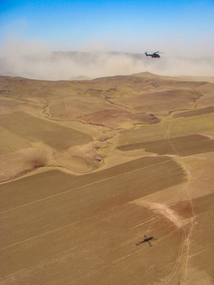 A helicopter and it's shadow, on the perched earth, below with a dust storm in the background.
