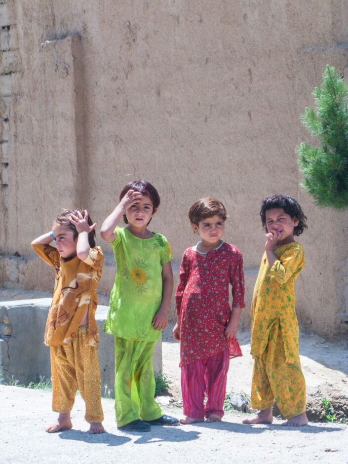 Four Afghan girls in colourful outfits standing by the side of the road in the vicinity of the governor's house in Lashkar-Gah, the provincial capital of Helmand province, Afghanistan.