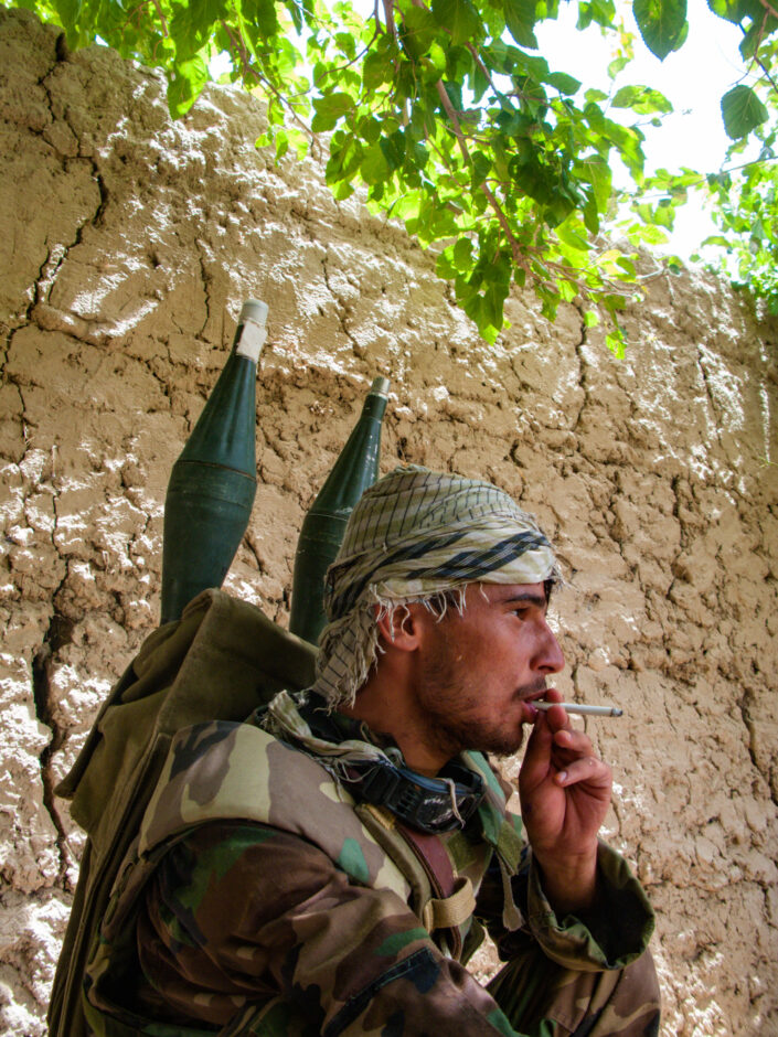 Afghan National Army soldier, with rocket heads attached to his back, having a cigarette break while on patrol in the Green Zone in Helmand, Afghanistan.