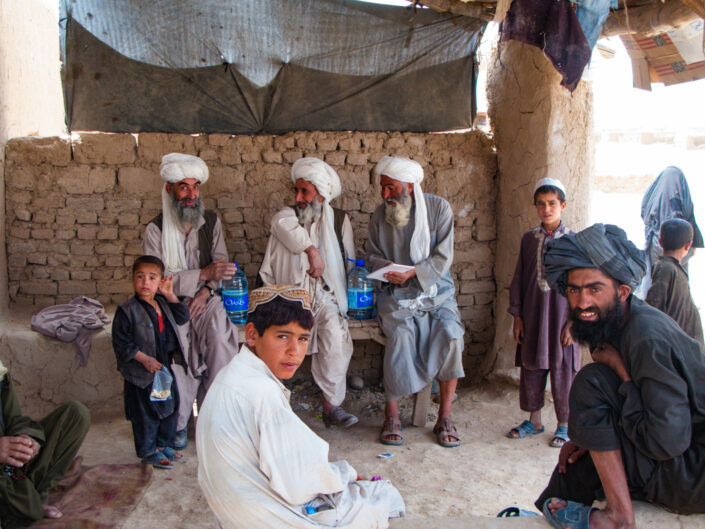 Village elders sit in a mud makeshift building surrounded by younger generations while a female dressed in a burkha walks past, in Lashkar Gah, Helmand, Afghanistan