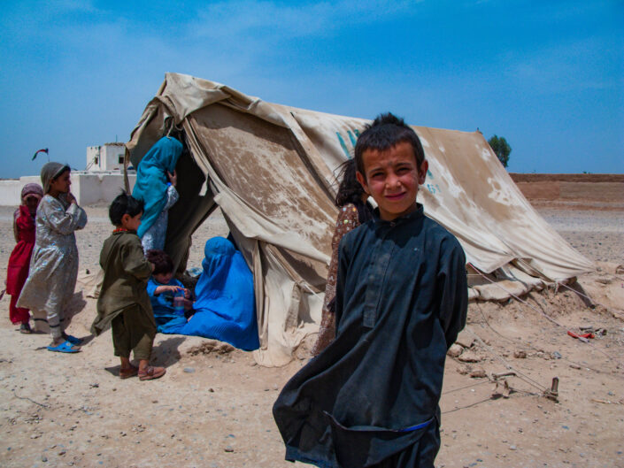 Boy standing in front of a dust covered tent full of women and children