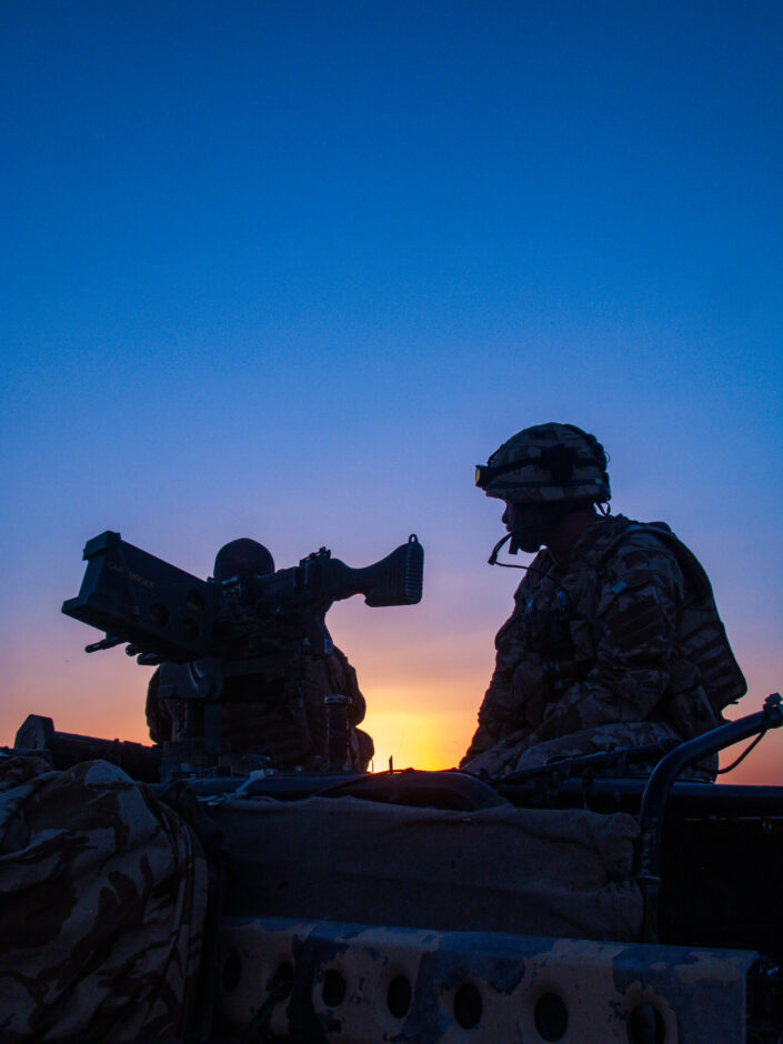 British Army soldier conducting top cover, at dusk in the desert outside the Marjah district, during a vehicle patrol in Helmand.