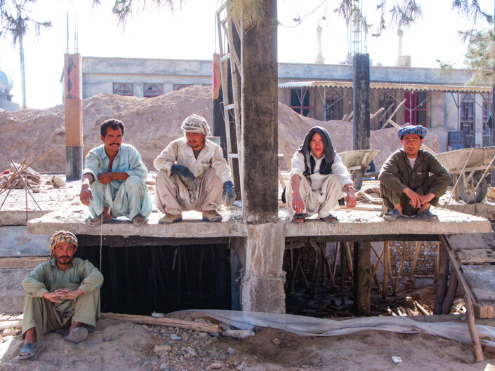 Construction workers sit on their haunches during a break on site in Lashkar- Gah, Helmand, Afghanistan