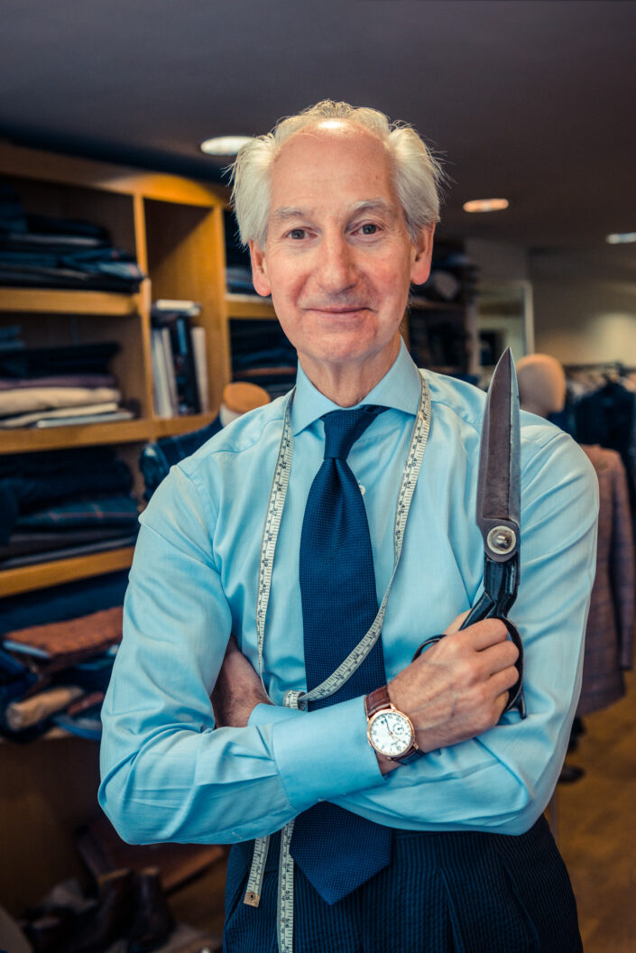 Male in pale blue shirt with a measuring tape around his neck holding a pair of tailoring scissors