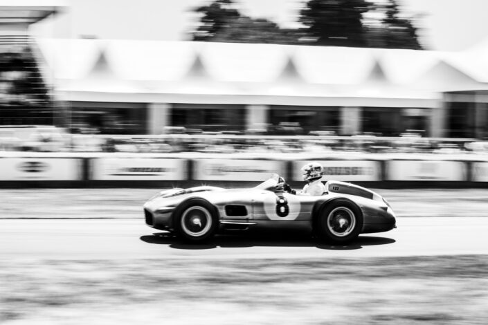 Classic Mercedes Benz racing on track with the grandstand in the background