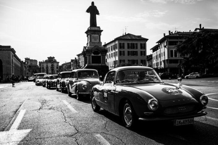 The Line Up; classic cars, led by a DKW Monza, lining up for a car rally in an Italian piazza