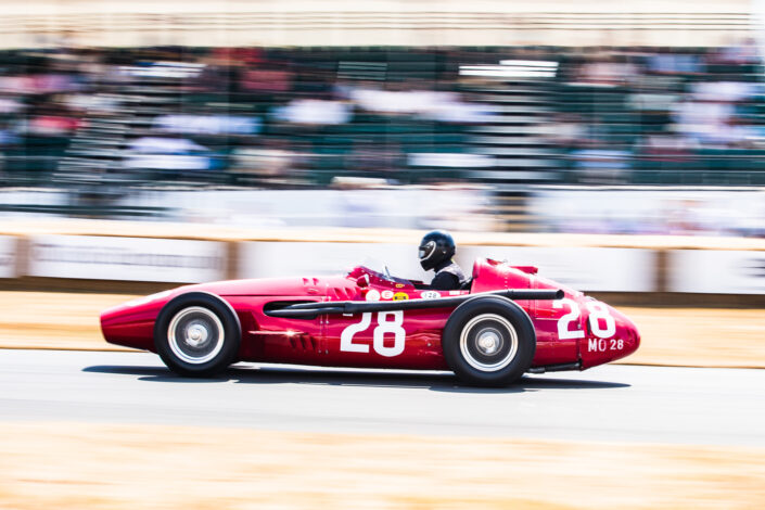 Red Maserati 250F on the track with the grandstand in the background